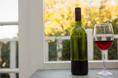 Red wine glass and bottle on table at bar Stock Photos
