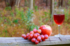 Red wine glass and bunch of grapes on wooden table Stock Photos