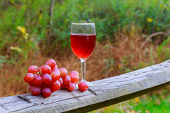 Red wine glass and bunch of grapes on wooden table Royalty Free Stock Images