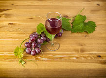Red wine glass and bunch of grapes on wooden table Stock Image