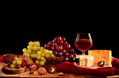 Red wine glass with cheese, grapes and nuts Stock Image