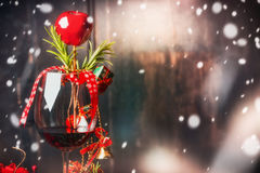 Red wine glass with Christmas decoration at dark wooden background with snow Stock Photos