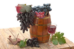 Red wine in a glass and a cluster of grapes Stock Images