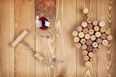 Red wine glass, corkscrew and grape shaped corks Royalty Free Stock Images