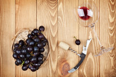 Red wine glass, corkscrew and grape Stock Images