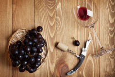 Red wine glass, corkscrew and grape Stock Photos