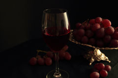 Red wine in glass and fresh grapes Stock Photos