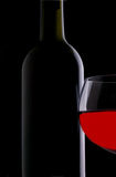 Red Wine Glass in Front of Bottle Stock Image