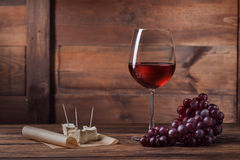Red wine in glass with grape and cheese on wood. En background stock photography