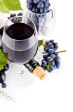 Red wine in glass with grapes. On white background stock photo