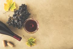 Red wine in a glass, grapes, bottle and cork on the table stock image