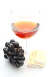 Red wine glass with grapes and cheese on white background Stock Photography