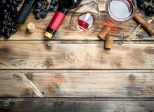 Red wine in a glass with grapes and a corkscrew. On a wooden background stock image