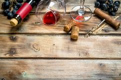 Red wine in a glass with grapes and a corkscrew. On a wooden background stock photography