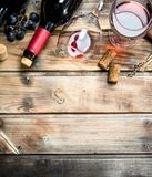 Red wine in a glass with grapes and a corkscrew. On a wooden background stock images