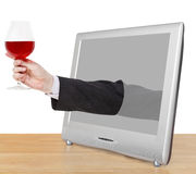 Red wine glass in male hand leans out TV screen Stock Photos