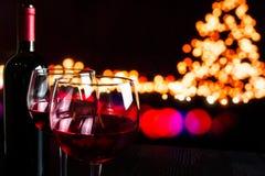 Red wine glass near bottle against bokeh lights background Stock Images
