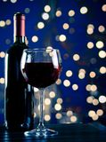 Red wine glass near bottle with light blue bokeh Royalty Free Stock Images