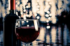 Red wine glass near bottle with light bokeh. In background stock photography