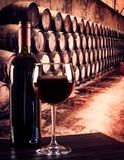 Red wine glass near bottle in old wine cellar background. Red wine glass near bottle in the old wine cellar with barrels background Royalty Free Stock Images