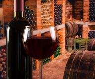 Red wine glass near bottle on old wine cellar background with space for text. Red wine glass near bottle in the old wine cellar background with barrels with Stock Photos