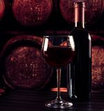 Red wine glass near bottle on wood table and in old wine cellar background. Red wine glass near bottle on wood table and in the old wine cellar with barrels Stock Image