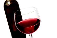 Red wine glass near wine bottle Stock Image