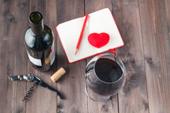 Red wine glass and notebook on table Royalty Free Stock Photo