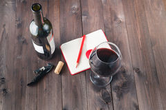 Red wine glass and notebook on table Stock Photo