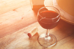 Red wine glass and old book on wooden table at sunset burst. vintage filtered image Stock Photos