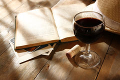 Red wine glass and old book on wooden table at sunset burst. vintage filtered image.  Royalty Free Stock Images
