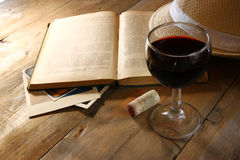 Red wine glass and old book on wooden table at sunset burst. vintage filtered image Royalty Free Stock Photo