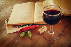 Red wine glass and old book on wooden table at sunset burst. vintage filtered image Stock Image