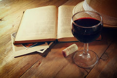 Red wine glass and old book on wooden table at sunset burst. vintage filtered image Royalty Free Stock Photography