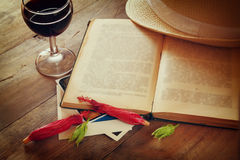 Red wine glass and old book on wooden table at sunset burst. vintage filtered image Stock Photography