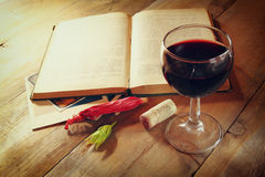 Red wine glass and old book on wooden table at sunset burst. vintage filtered image.  Stock Photo