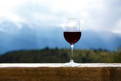 Red wine glass at a picnic standing on a wooden table in front of beautiful mountain background Royalty Free Stock Photos