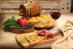 Red wine in a glass and pomegranate cheese cake on wooden table Royalty Free Stock Images