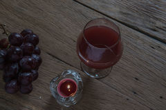 Red wine in glass for a romantic and  candle on wooden table. Stock Photo