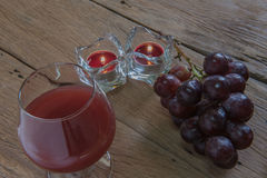 Red wine in glass for a romantic and  candle on wooden table. Stock Image