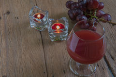 Red wine in glass for a romantic and  candle on wooden table. Royalty Free Stock Images
