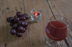 Red wine in glass for a romantic and  candle on wooden table. Stock Images