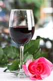 Red wine glass with rose, bright background Royalty Free Stock Photo