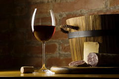 Red wine glass in rural kitchen. Cutting board with genuine Italian food in a rural kitchen. Red wine glass, ripe hard cheese from ewe's milk and sausage. Warm royalty free stock photography