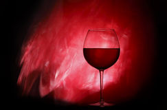 Glass with red wine. Red wine glass on the shining background Royalty Free Stock Image