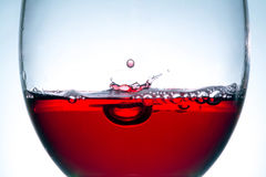 Red wine in glass, splashing, splash, wave of red wine close up Royalty Free Stock Photos