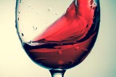 Red wine in glass, splashing, splash, wave of red wine close up Stock Image