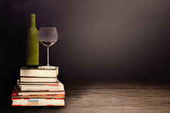 Red wine and glass standing on pile of books Stock Photo