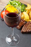 Red wine glass and steak with grilled potato, corn, salad Stock Photo