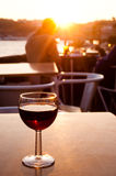 Red wine glass at sunset. A full glass of red Porto wine on a table in a bar in Portugal at sunset royalty free stock image